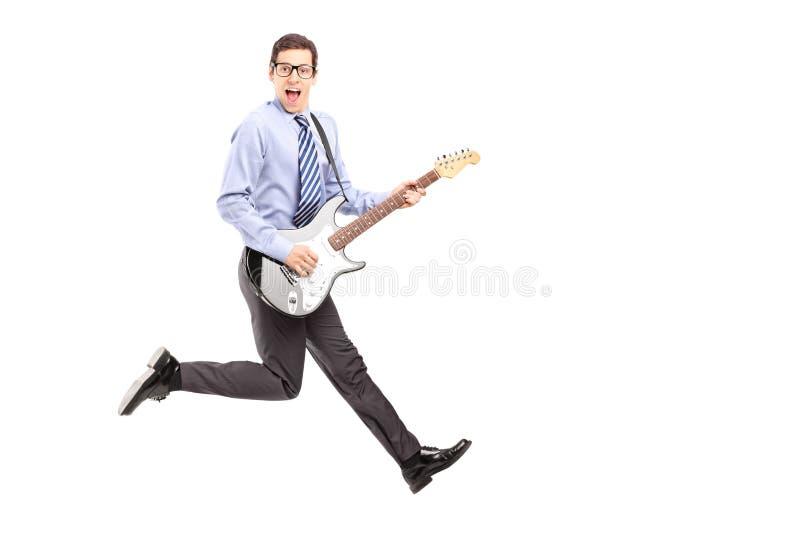 Volledig lengteportret van energiek jong mannetje die met een guit springen stock foto