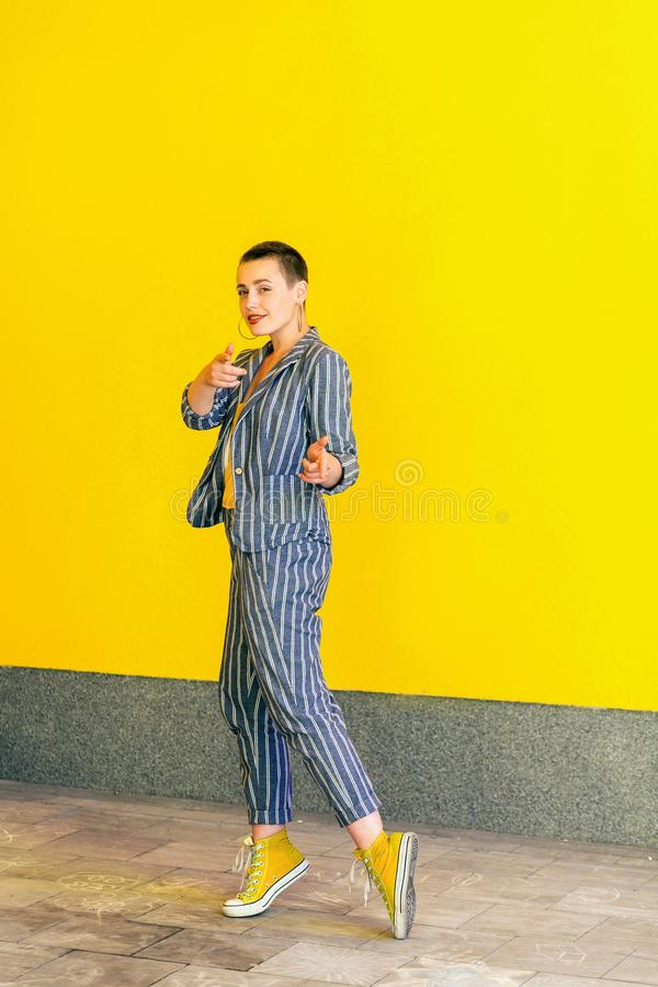 Volledig lengteportret van gelukkige jonge korte haar mooie vrouw in geel overhemd, toevallig stijl gestreept kostuum die en bevi stock afbeelding