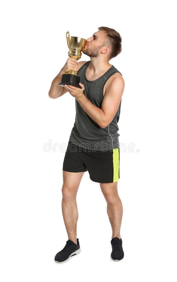 Volledig lengteportret van gelukkige jonge sportman die gouden trofeekop kussen stock foto's
