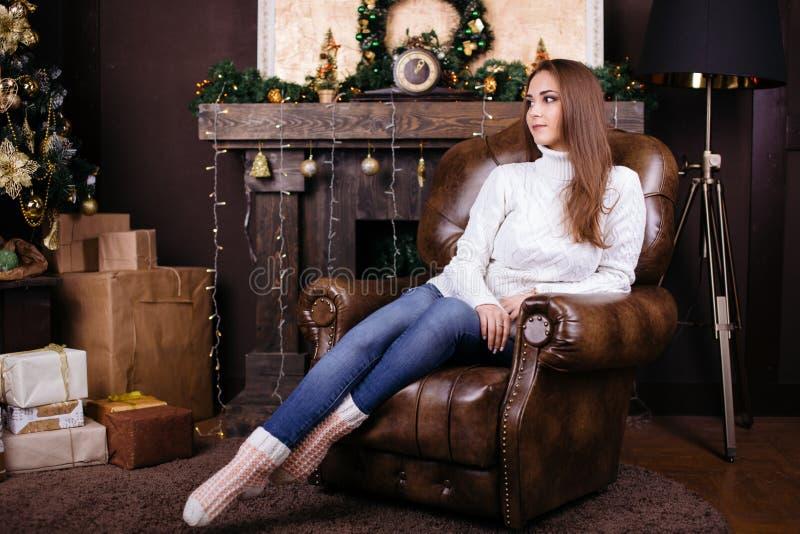 Volledig lengteportret van gelukkige jonge vrouwenzitting dichtbij Kerstmisboom royalty-vrije stock foto's