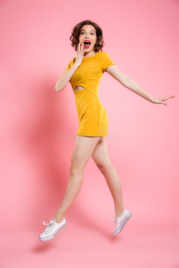 Volledig lengteportret van gelukkige weggegaane vrouw in elegante gele dre royalty-vrije stock afbeelding