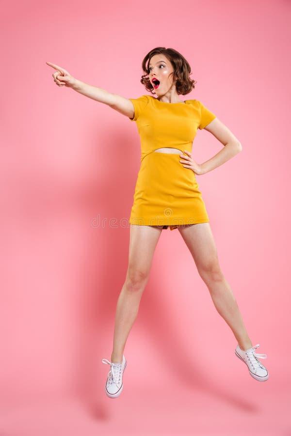 Volledig lengteportret van geschokte charmante donkerbruine vrouw met han stock foto