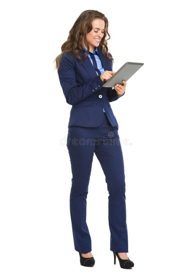 Volledig lengteportret van het gelukkige bedrijfsvrouw werken met tablet royalty-vrije stock afbeelding