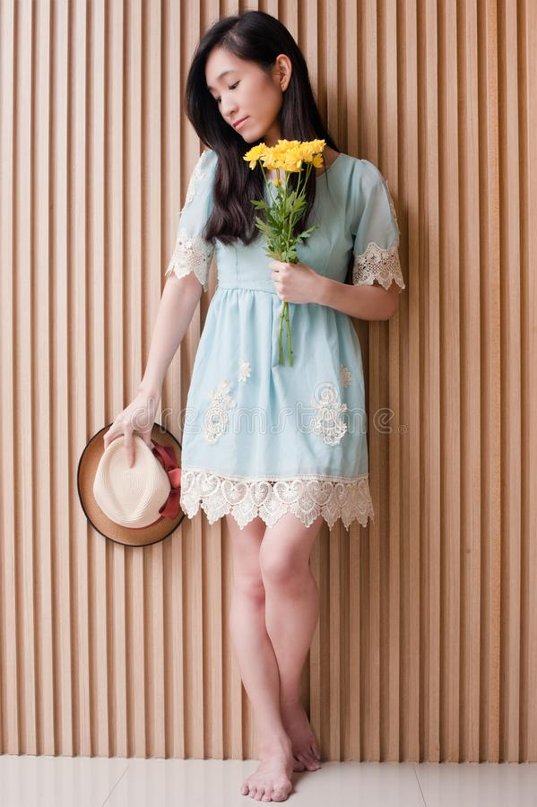 Volledig lengteportret van het glimlachen van de Aziatisch hoed van de meisjesholding en boeket van gele bloemen tegen houten muu stock afbeeldingen