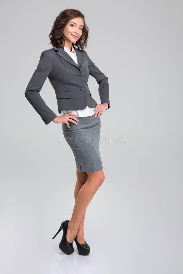 Volledig lengteportret van het jonge gelukkige vrouw stellen in formalwear stock afbeeldingen