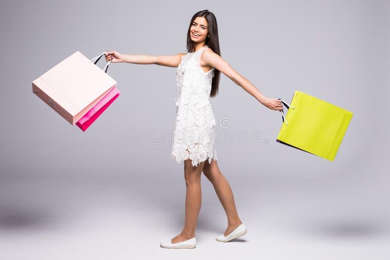 Volledig lengteportret van het mooie jonge die vrouw stellen met het winkelen zakken, op grijze achtergrond wordt geïsoleerd royalty-vrije stock foto