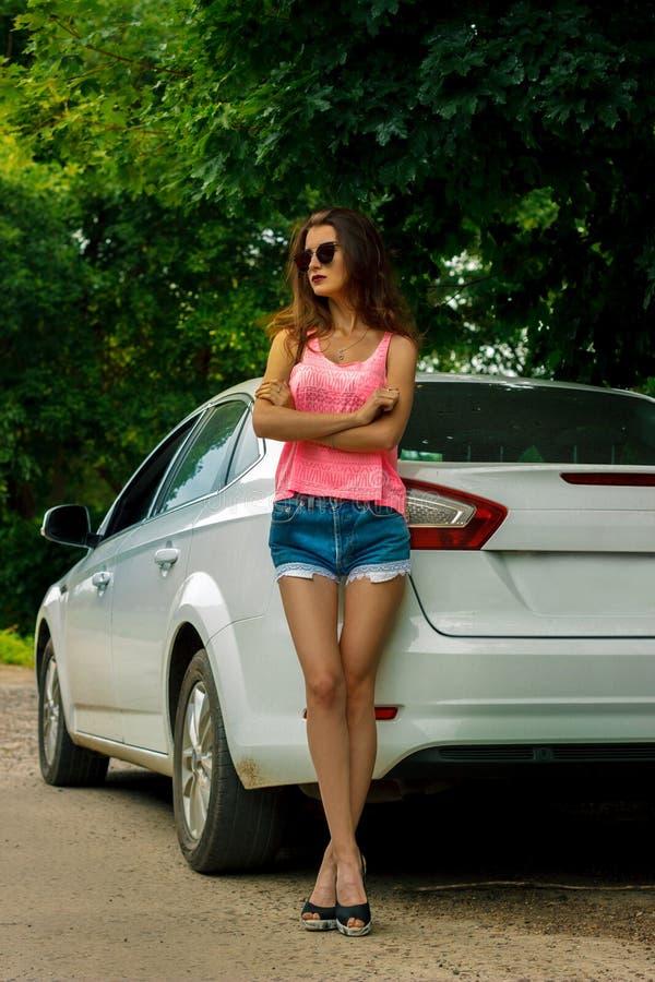 Volledig lengteportret van jong glamourbrunette stans over een witte auto stock foto's