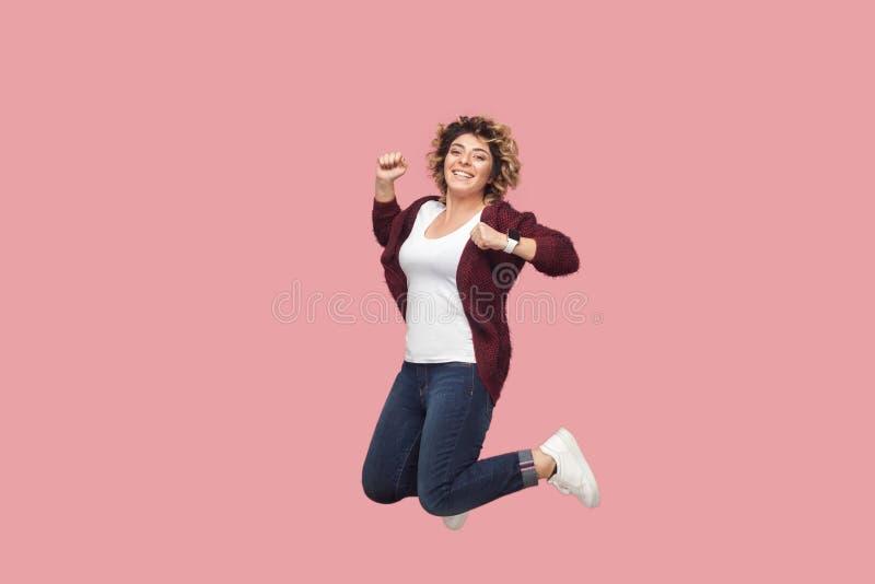 Volledig lengteportret van jonge gelukkige vrouw met krullend kapsel in wit overhemd die, en celebraiting bekijken bij springen t stock afbeelding