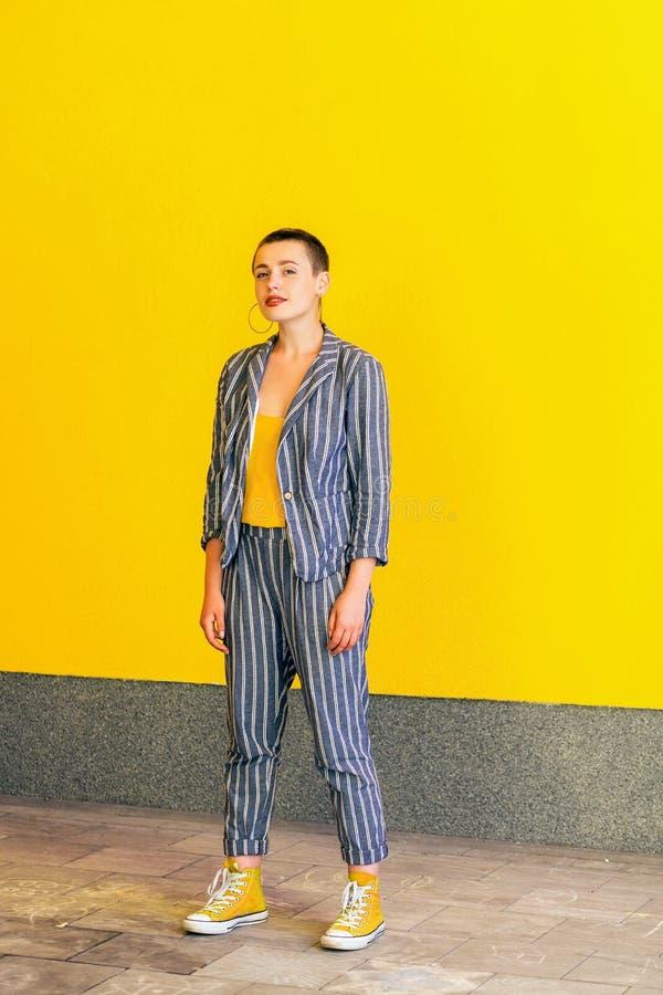 Volledig lengteportret van jonge korte haar mooie vrouw in geel overhemd en toevallig stijl gestreept kostuum die en bevinden bek stock afbeelding
