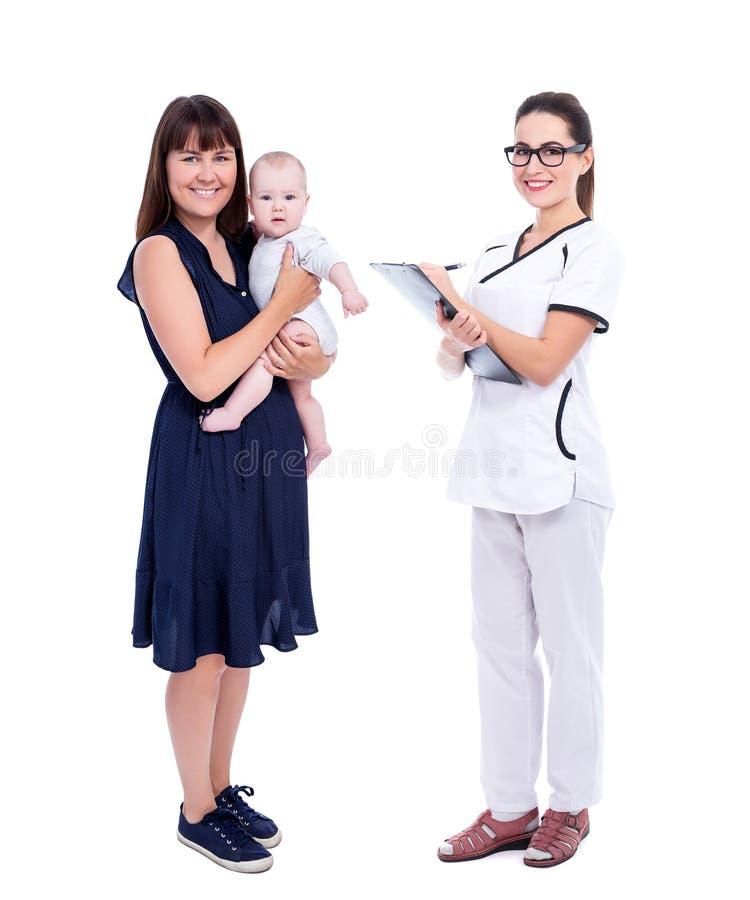 Volledig lengteportret van jonge moeder met weinig baby en vrouwelijke die arts of verpleegster op wit wordt geïsoleerd stock fotografie