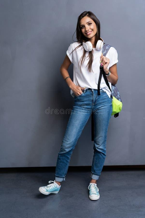Volledig lengteportret van jonge mooie vrouw Glimlachend studentenmeisje die op een reis gaan Ge?soleerdu op grijze achtergrond stock fotografie