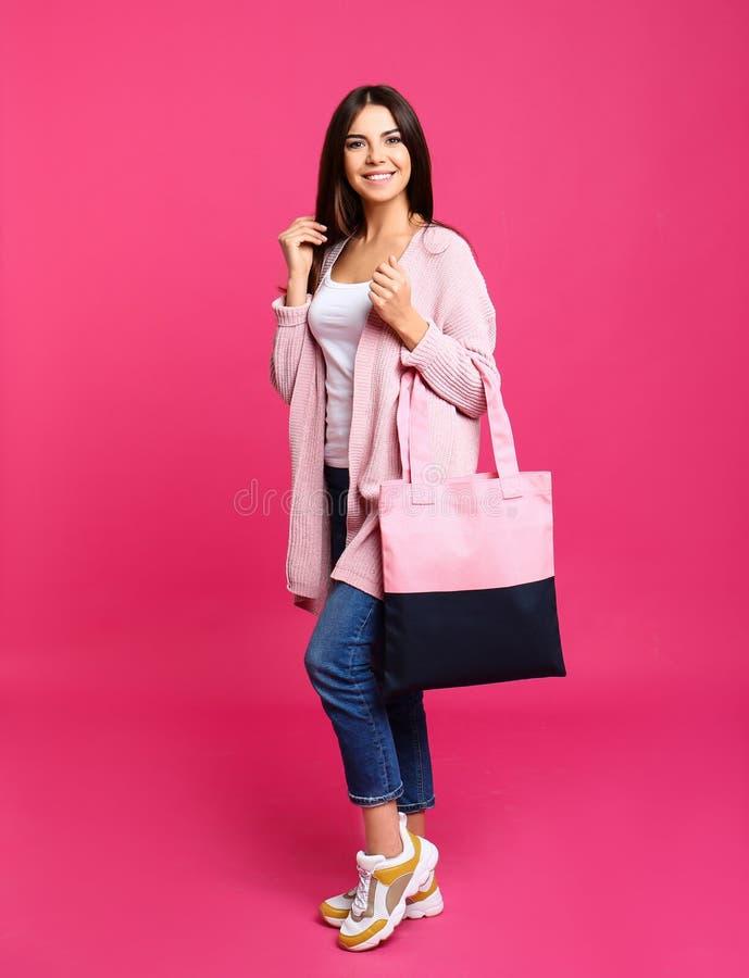Volledig lengteportret van jonge vrouw met textielzak stock afbeeldingen