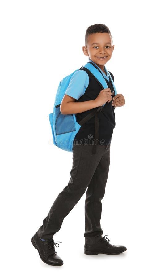 Volledig lengteportret van leuke Afrikaans-Amerikaanse jongen in school eenvormig met rugzak op wit stock foto's