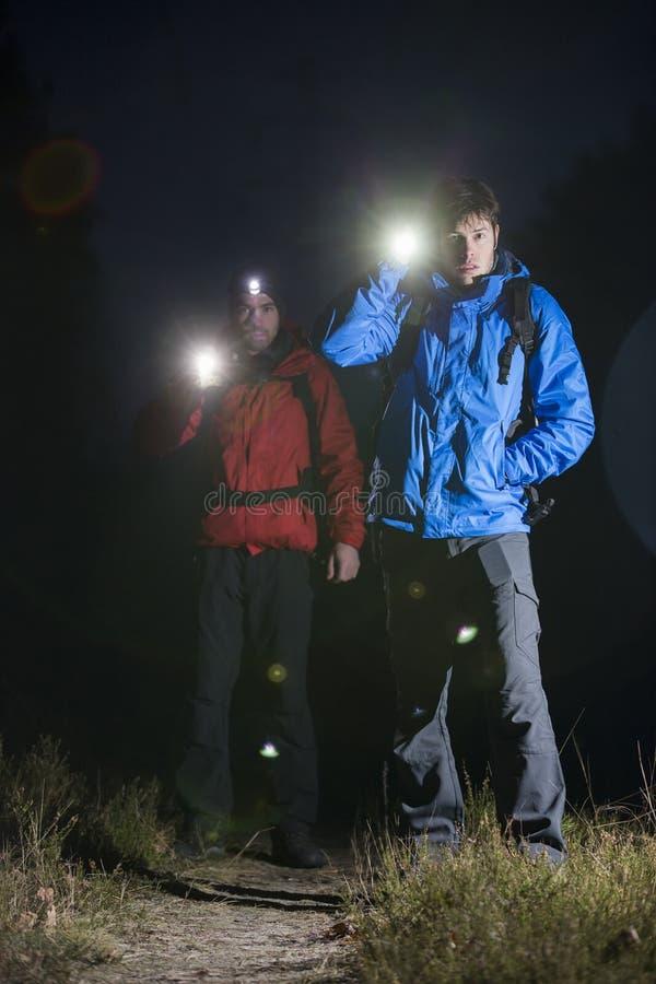 Volledig lengteportret van mannelijke backpackers met flitslichten op gebied bij nacht stock foto's