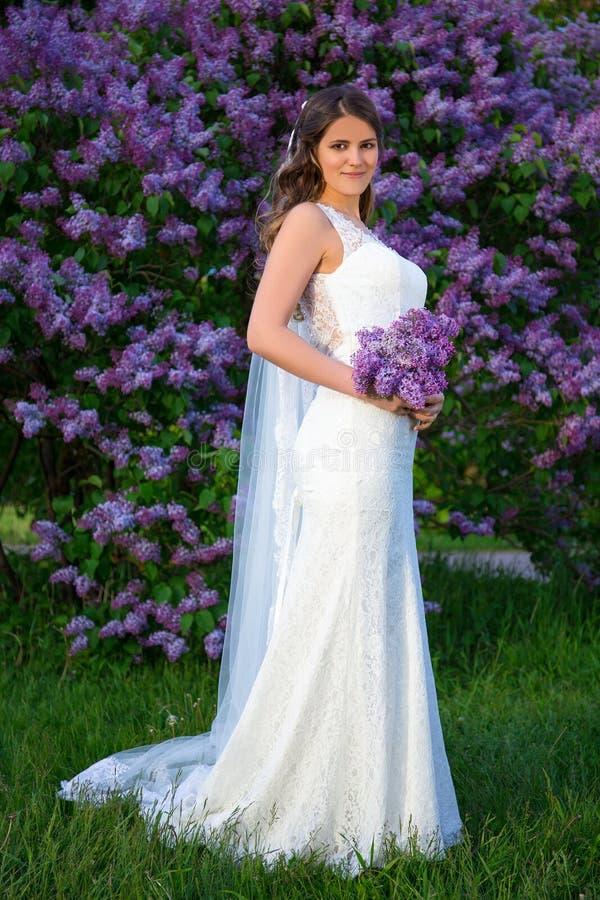 Volledig lengteportret van mooie bruid met lange sluier status stock fotografie