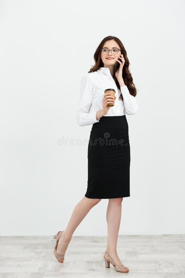 Volledig lengteportret van mooie jonge bedrijfsvrouw in formele slijtage die en voor celtelefoon lopen spreken met meeneem royalty-vrije stock afbeelding