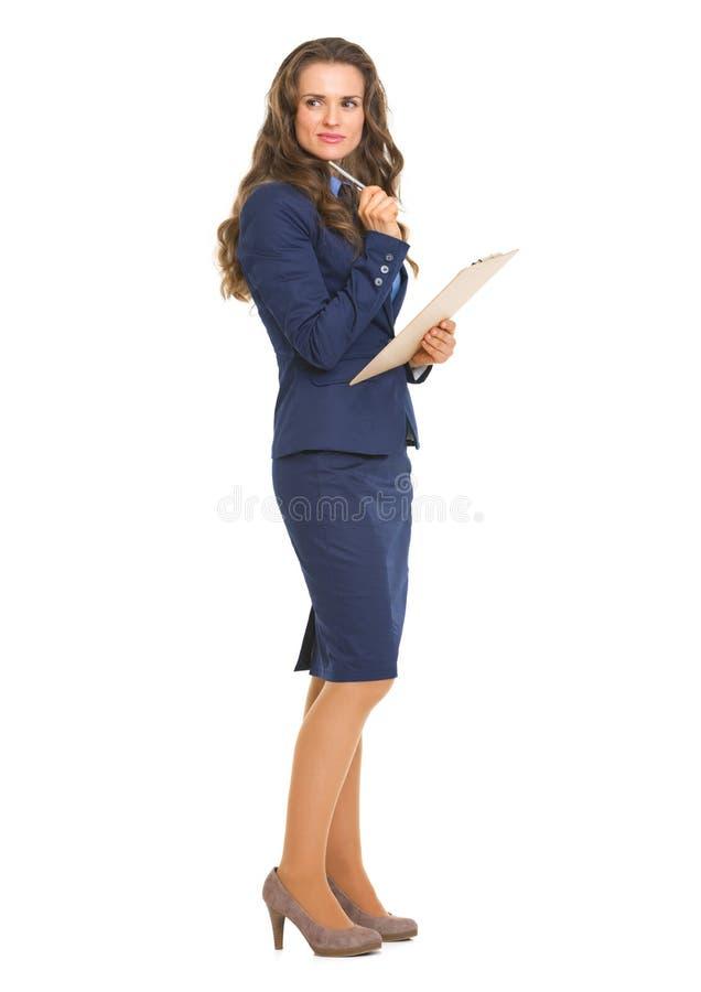 Volledig lengteportret van nadenkende bedrijfsvrouw met klembord stock foto's
