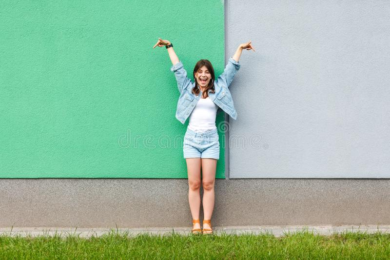 Volledig lengteportret van opgewekte mooie vrouw in de toevallige stijl van het jeansdenim in zomer die en zich op groen bevinden stock foto's