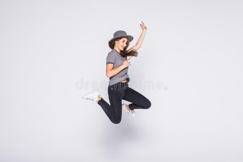 Volledig lengteportret van tevreden Amerikaanse vrouw die jeans en t-shirt springen dragen ge?soleerd over witte achtergrond royalty-vrije stock afbeelding