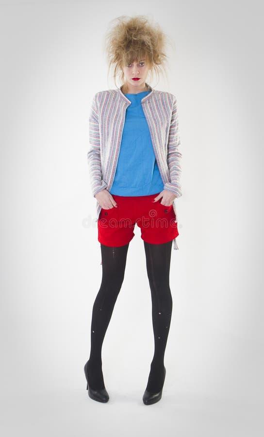 Volledig lengteportret van vrouw het stellen in rode borrels en blauwe sweater die toevallig jasje met een gekke haarstijl dragen stock fotografie