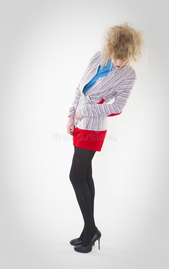 Volledig lengteportret van vrouw het stellen in rode borrels en blauwe sweater die toevallig jasje met een gekke haarstijl dragen royalty-vrije stock foto