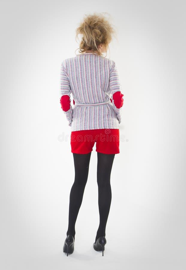 Volledig lengteportret van vrouw het stellen in rode borrels en blauwe sweater die toevallig jasje met een gekke haarstijl dragen royalty-vrije stock afbeelding