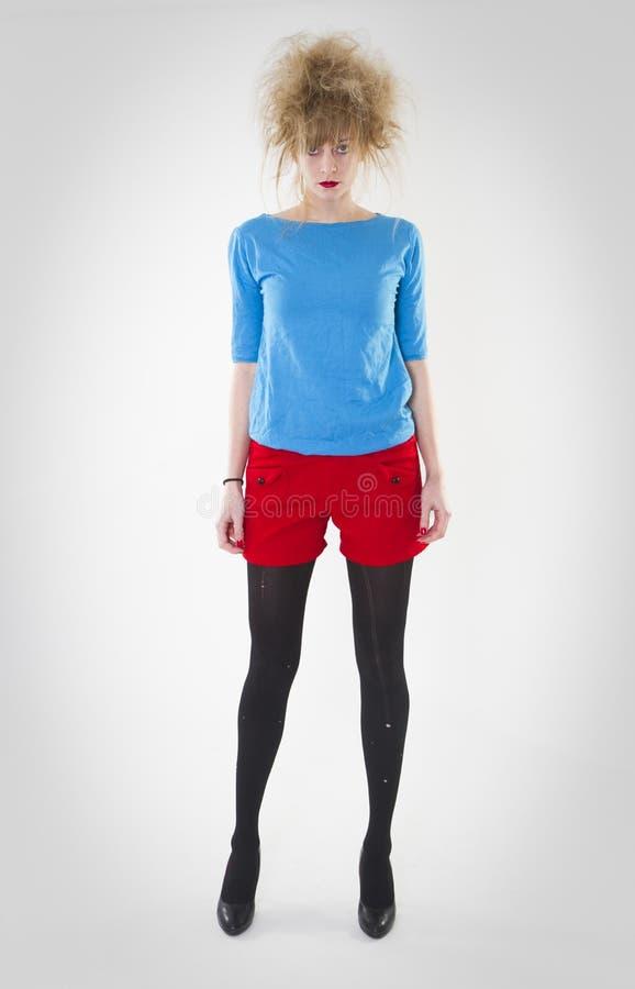 Volledig lengteportret van vrouw het stellen in rode borrels en blauwe sweater met een gekke haarstijl r stock foto's