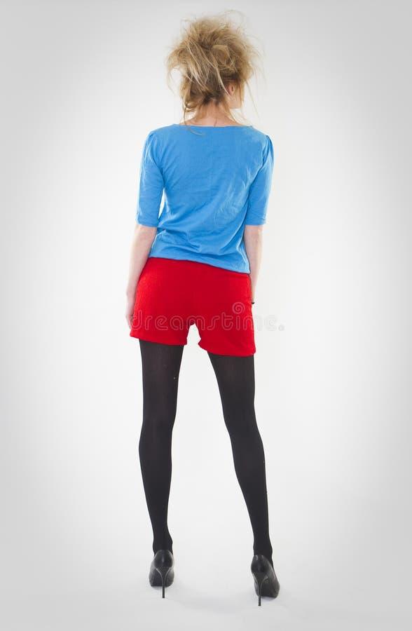 Volledig lengteportret van vrouw het stellen in rode borrels en blauwe sweater met een gekke haarstijl r royalty-vrije stock fotografie