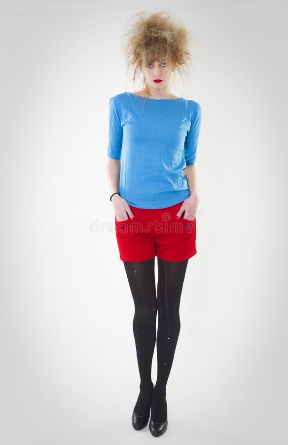 Volledig lengteportret van vrouw het stellen in rode borrels en blauwe sweater met een gekke haarstijl r royalty-vrije stock afbeeldingen