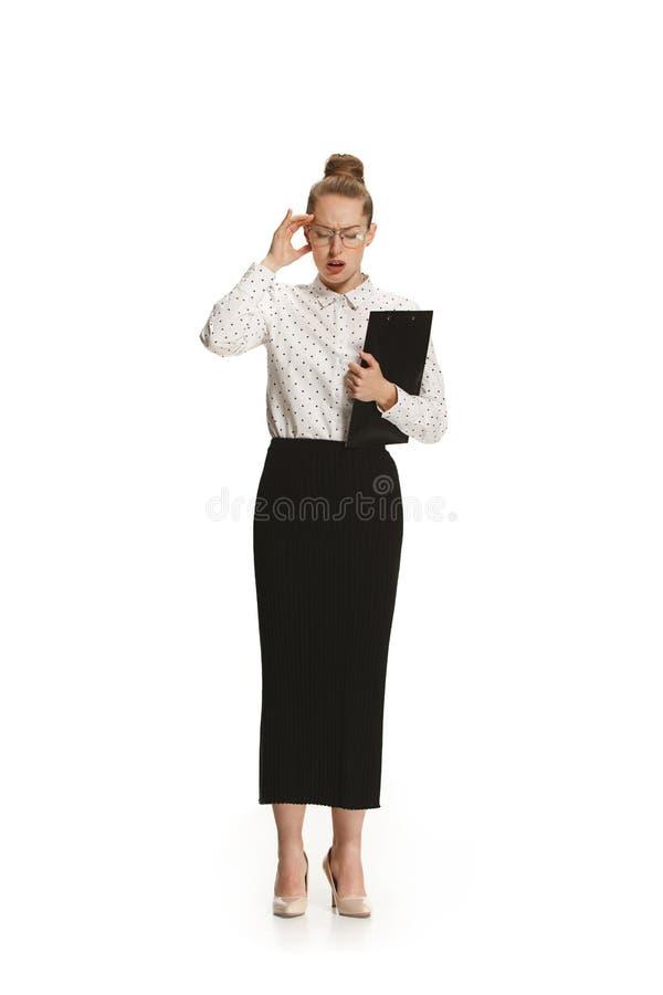 Volledig lengteportret van vrouwelijke leraar met een hoofdpijn die een omslag houden die tegen witte achtergrond wordt geïsoleer royalty-vrije stock afbeeldingen