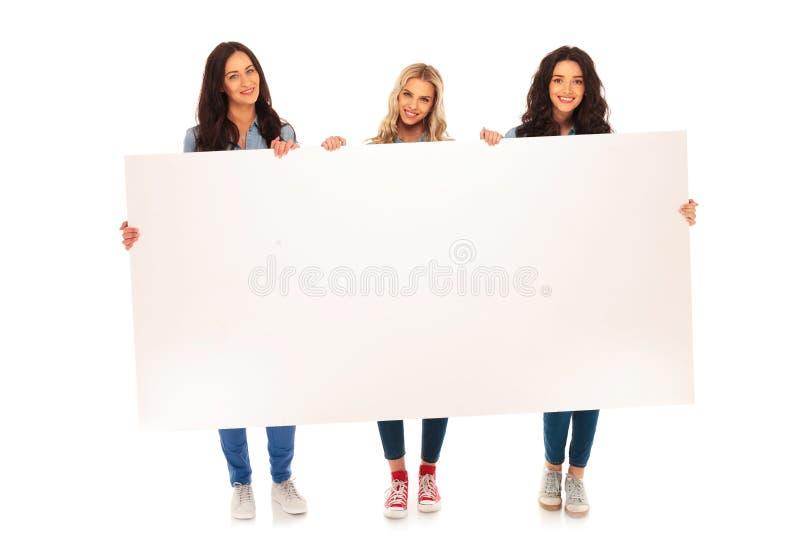 Volledig lichaamsbeeld van drie toevallige vrouwen die groot aanplakbord houden royalty-vrije stock afbeeldingen