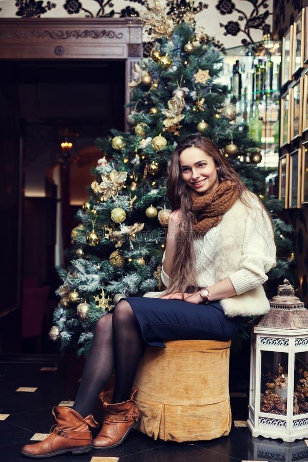 Volledig lichaamsportret van een jonge mooie het glimlachen vrouwenzitting dichtbij de Kerstboom stock foto