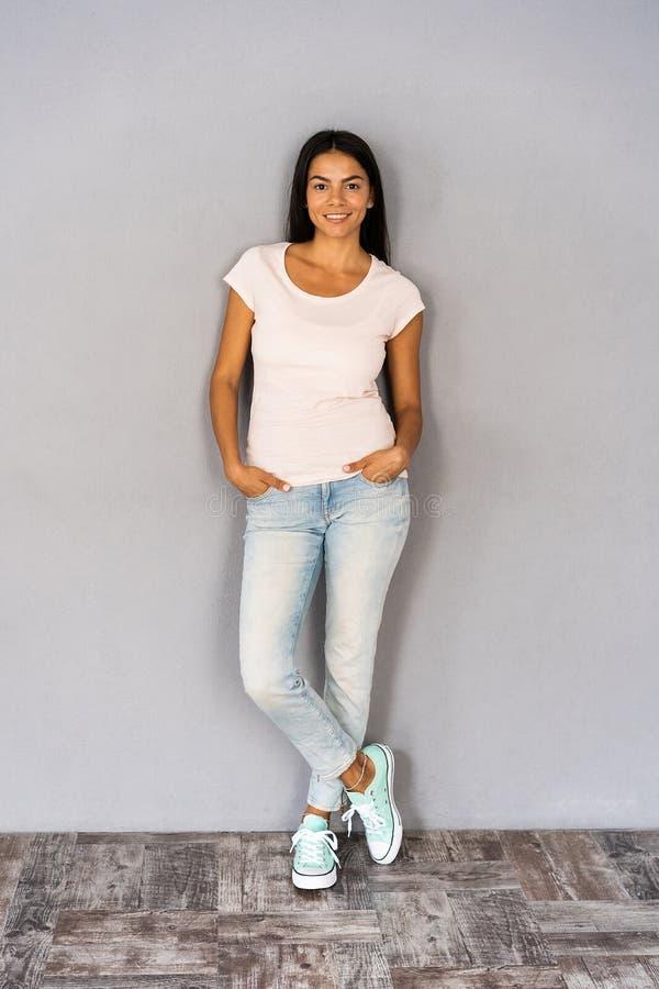 Volledig lichaamsportret van gelukkige glimlachende mooie jonge die vrouw, over grijze achtergrond wordt geïsoleerd stock foto's