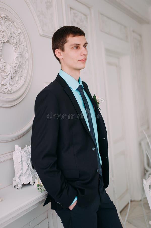 Volledig lichaamsportret van jonge modieuze zakenman in band en vest met handen op taille royalty-vrije stock foto