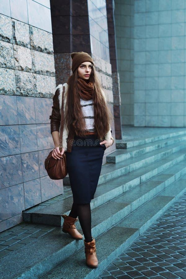 Volledig lichaamsportret van jonge mooie modieuze vrouw die modieuze kleren dragen die bij de straat lopen Modelleer het kijken stock foto