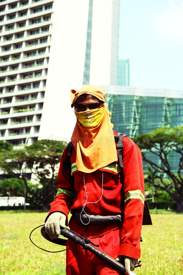 Volledig omvatte maaiende arbeider in Singapore stock afbeeldingen