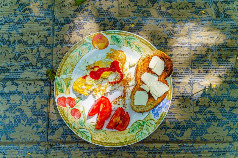 Volledig ontbijt - de gebraden eieren, ketchup, sneden tomaat, geroosterde plak van wit brood met plakken van boter op een witte  stock fotografie