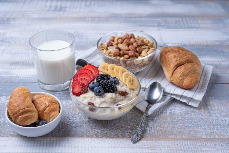 Volledig ontbijt van havermoutpap met bessen en noten, croissant, melk op witte houten achtergrond royalty-vrije stock fotografie