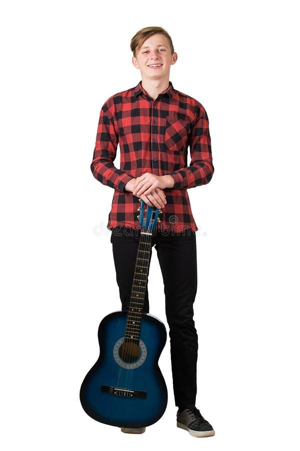 Volledig portret van een vrolijke tienerjongen die poselt met zijn favoriete blauwe akoestische gitaar geïsoleerd op witte achter royalty-vrije stock afbeelding