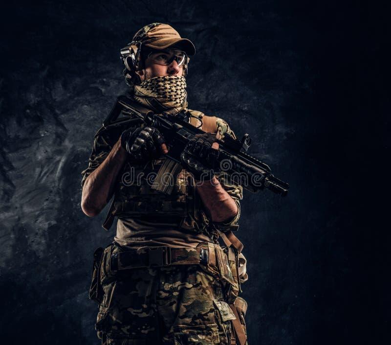 Volledig uitgeruste militair in camouflage eenvormige holding een aanvalsgeweer Studiofoto tegen een donkere muur stock afbeelding