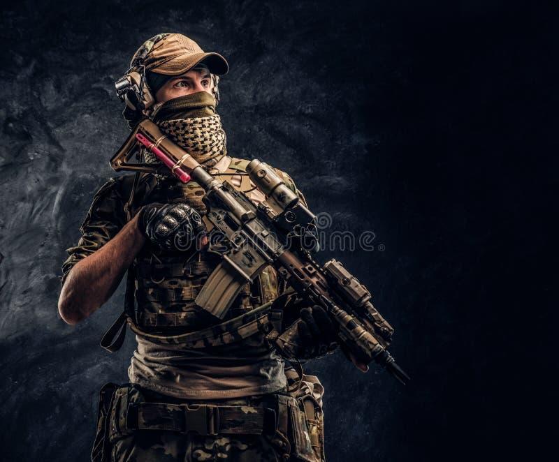 Volledig uitgeruste militair in camouflage eenvormige holding een aanvalsgeweer Studiofoto tegen een donkere muur royalty-vrije stock foto