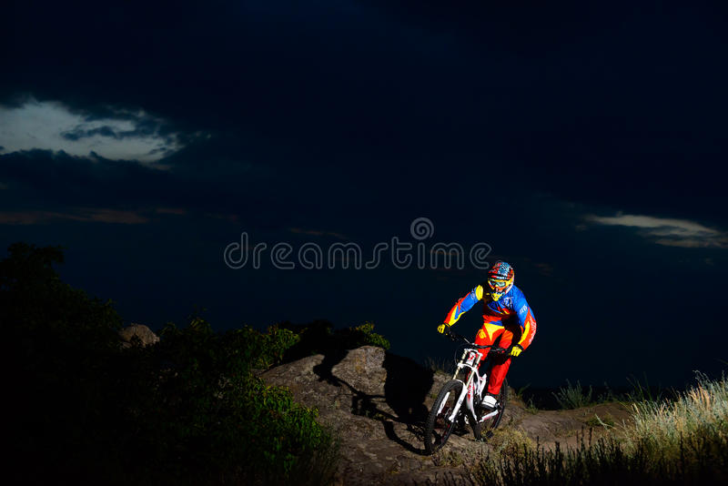 Volledig Uitgeruste Professionele bergaf Fietser die de Fiets berijden op de Nacht Rocky Trail stock foto's