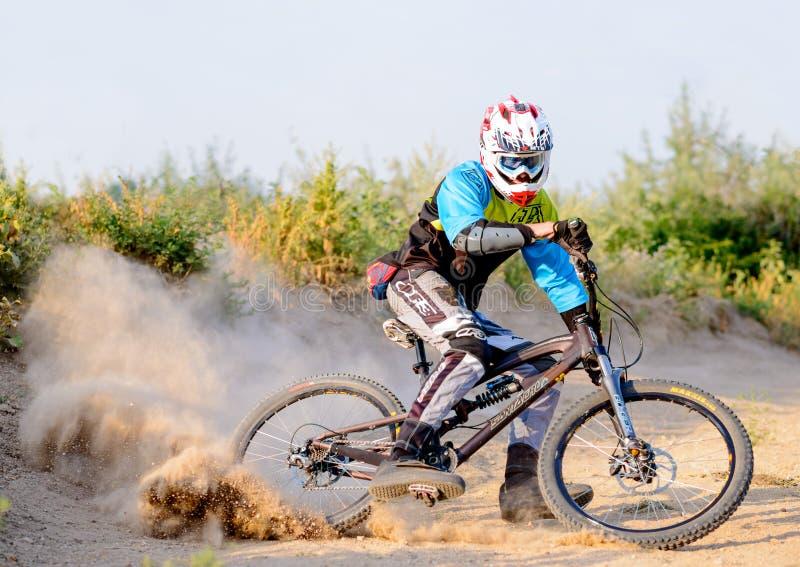 Volledig Uitgeruste Professionele bergaf Fietser die de Fiets berijden op Dusty Trail Extreme sporten royalty-vrije stock foto