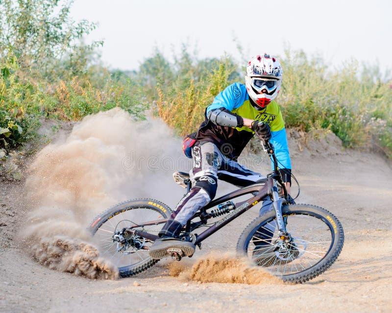 Volledig Uitgeruste Professionele bergaf Fietser die de Fiets berijden op Dusty Trail Extreme sporten royalty-vrije stock afbeelding