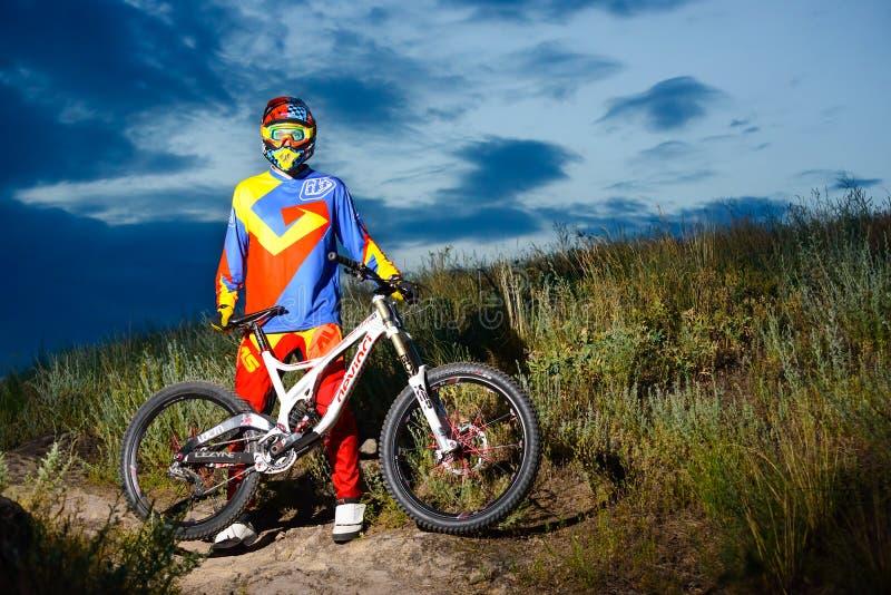 Volledig Uitgeruste Professionele bergaf Fietser met Fiets op de Nacht Rocky Trail royalty-vrije stock afbeeldingen