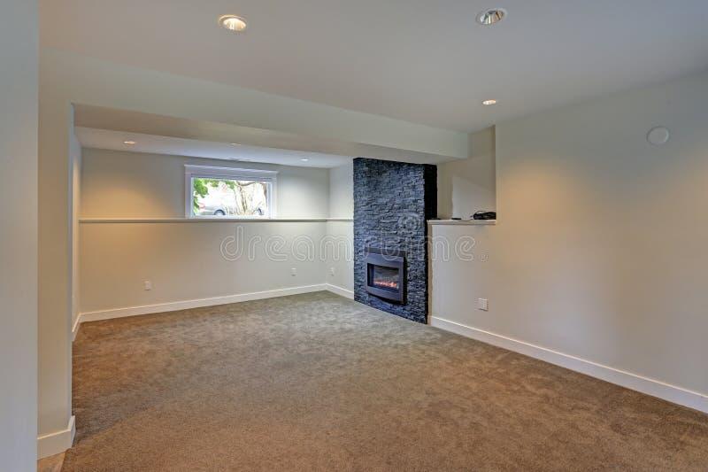 Volledig vernieuwd kelderverdiepingsgebied met zwarte open haard stock afbeelding