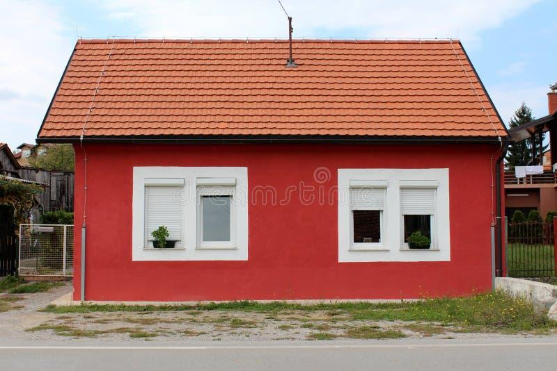 Volledig vernieuwd klein familiehuis in de voorsteden met nieuwe die vensters en daktegels met ongesneden gras en grint worden om stock afbeelding