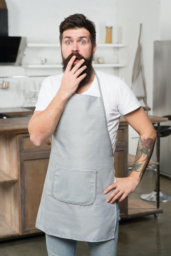 Volledig zijnd bij een verlies Verraste kok die zijn open mond behandelen met hand Gebaarde mens die kokschort in keuken dragen royalty-vrije stock afbeeldingen