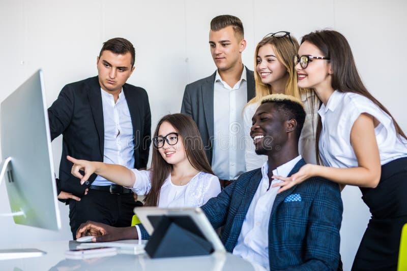 Volledige concentratie op het werk Groep jonge bedrijfs en mensen die terwijl samen het zitten bij het bureau werken communiceren stock foto's