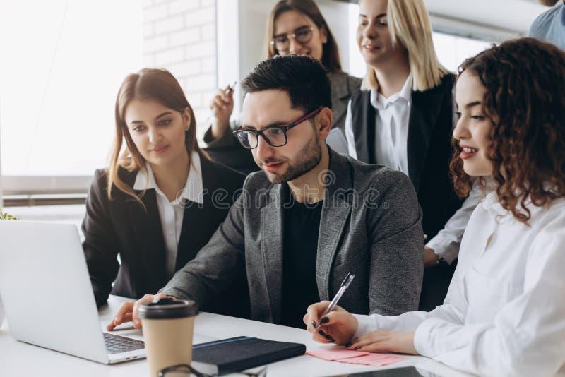 Volledige concentratie op het werk Groep jonge bedrijfs en mensen die terwijl samen het zitten bij het bureau werken communiceren stock fotografie
